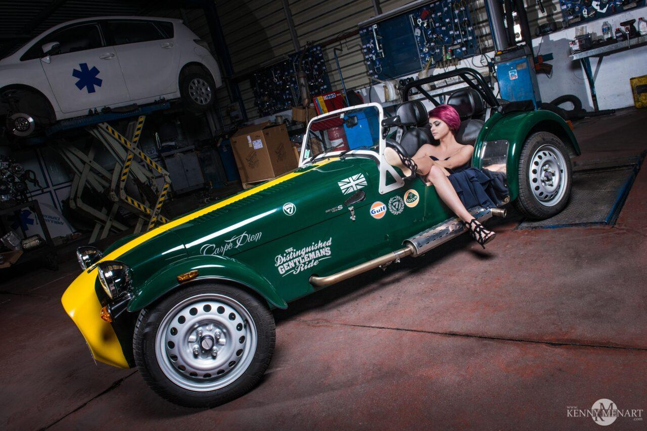 Fille au volant d'une caterham verte et jaune dans un garage