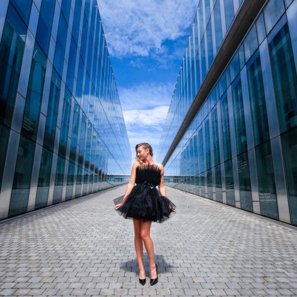photo de mode en extérieur avec vitrage et reflet robe noire et perspective ligne de fuite