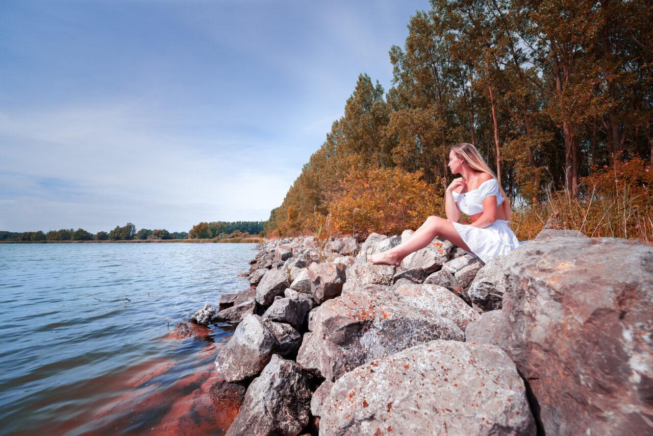 Photographie paysage automnal au bord d'un lac avec un jeune fille sur les rochers